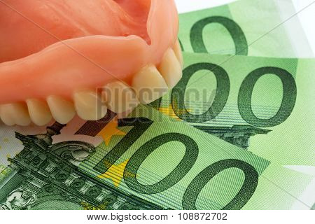 denture and euro notes, symbolic photograph of dentures, treatment costs and payment
