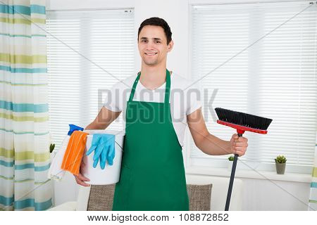 Happy Man In Green Apron Holding Cleaning Equipment At Home