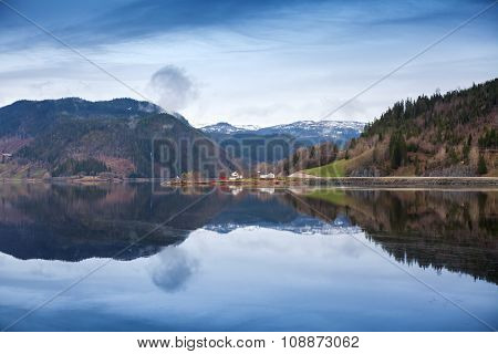Rural Norwegian Landscape With Still Lake Water