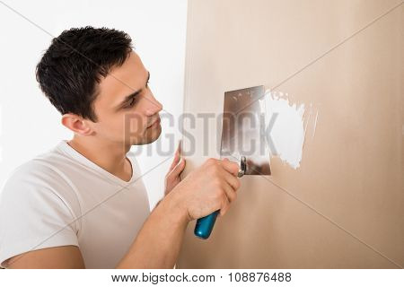 Man Using Putty Knife On White Wall