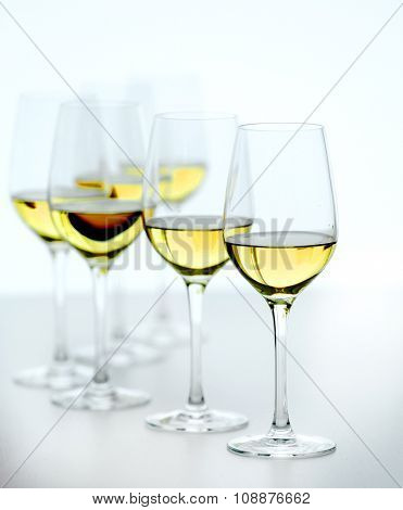 Wineglasses with white wine on wooden table on bright background
