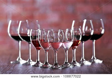 Wineglasses with white, red and pink wine on wooden table on wall brick background