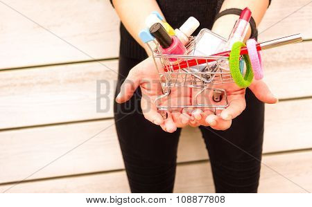Young woman holding little trolley with makeup inside - Female hands with make up and beauty product