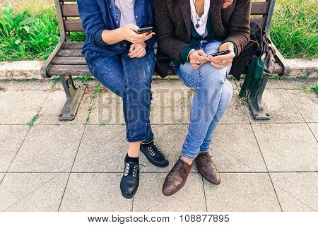 Couple Of Hipsters Holding Mobile Phone - Two  Trendy Guys Wifi Connected Sharing Web Content - Crop