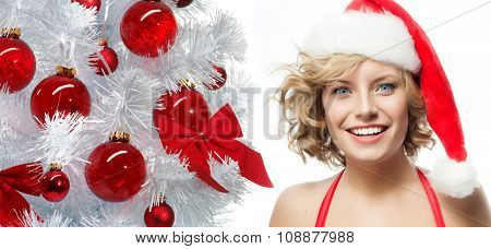 portrait of attractive  caucasian smiling woman blond isolated on white studio shot in santa's hat new year tree red balls