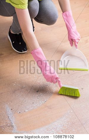 Person Cleaning Floor With Dustpan
