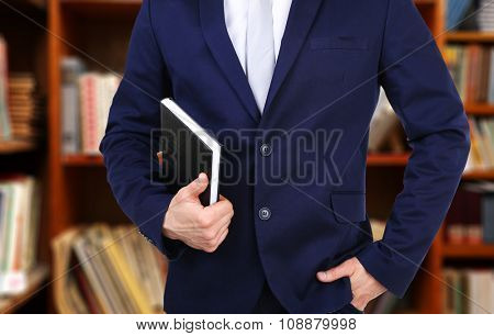 Male hand holding book on bookshelves background