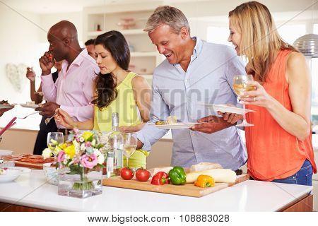 Group Of Mature Friends Enjoying Buffet At Dinner Party