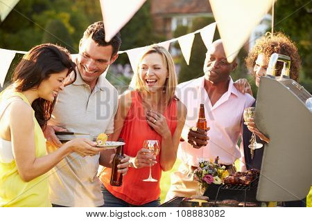 Mature Friends Enjoying Outdoor Summer Barbeque In Garden