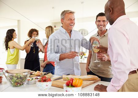 Group Of Mature Friends Enjoying Dinner Party At Home