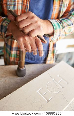 Close Up Of Stone Mason At Work On Carving In Studio