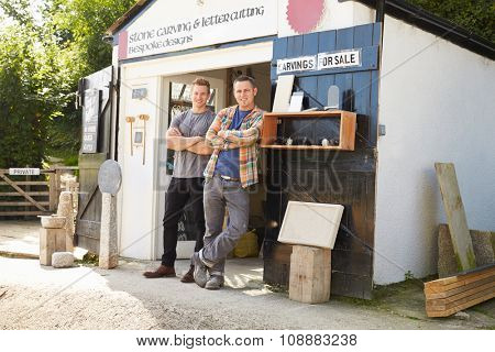 Portrait Of Stone Mason With Apprentice Outside Workshop
