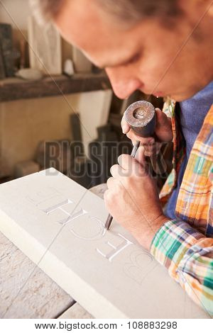 Stone Mason At Work On Carving In Studio