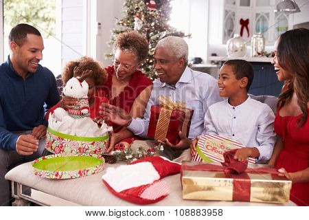 Family With Grandparents Opening Christmas Gifts