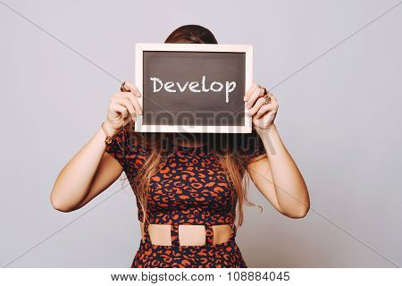 Young Woman Holding A Chalkboard Saying Develop