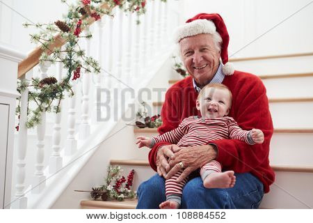 Grandfather With Granddaughter Sits On Stairs At Christmas