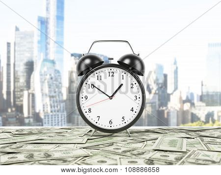An Alarm Clock Is Settled On The Surface Which Is Covered By Dollar Notes. New York Panorama On Back