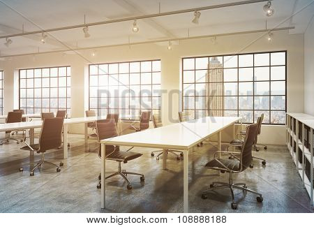 Workplaces In A Bright Sunset Loft Open Space Office. Empty Tables And Docents' Book Shelves. New Yo