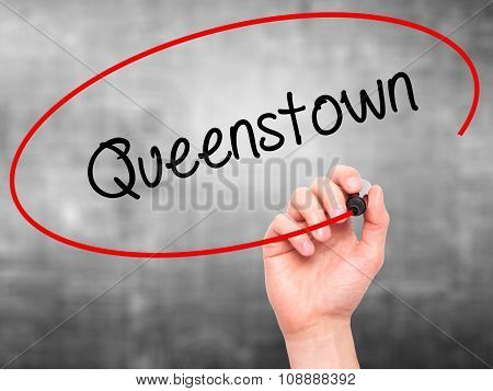Man Hand writing Queenstown with black marker on visual screen.