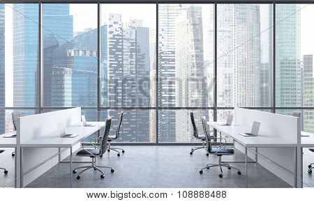 Workplaces In A Bright Modern Open Space Office. White Tables Equipped With Modern Laptops And Black