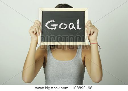 Young Woman Holding A Chalkboard Saying Goal.