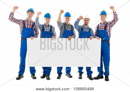 Male Carpenters With Arms Raised Holding Blank Billboard