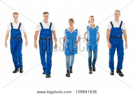 Portrait Of Confident Janitors Walking In Row
