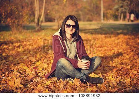 Girl With Coffee Sitting On Yellow Leaves