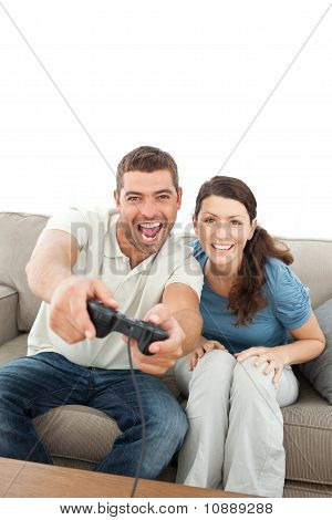 Happy Couple Playing Video Games Together Sitting On The Sofa