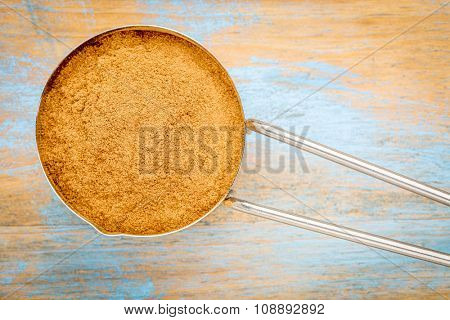 cinnamon  (cassia)  bark powder in a metal measuring scoop against painted wood