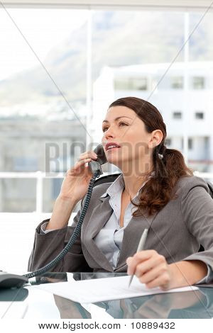 Serious Businesswoman Talking On The Phone And Taking Notes