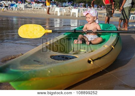 Little Smiling Child Sitting In An  Boat On The Beach.