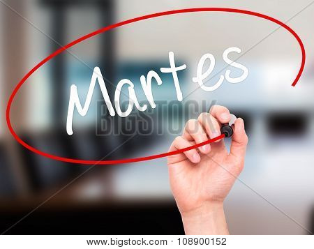 Man Hand writing Martes (Tuesday in Spanish) with black marker on visual screen.