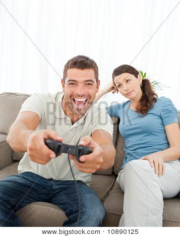 Bored Woman Looking At Her Boyfriend Playing Video Game On The Sofa