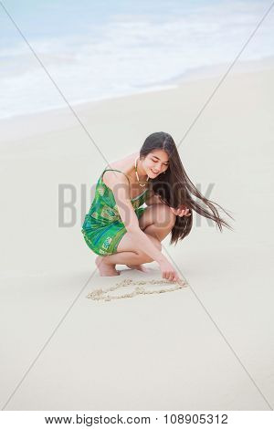 Beautiful Teen Girl Drawing Heart In Sand On Tropical Beach
