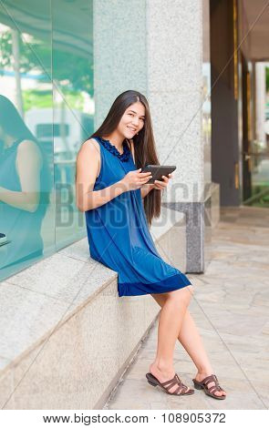 Biracial Teen Girl Holding Tablet Sitting Outside Store Window