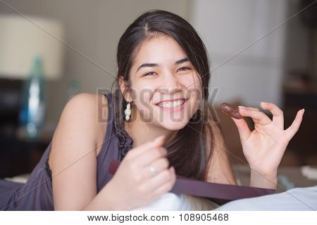 Biracial Teen Girl Lying On Bed Holding Chocolates, Smiling