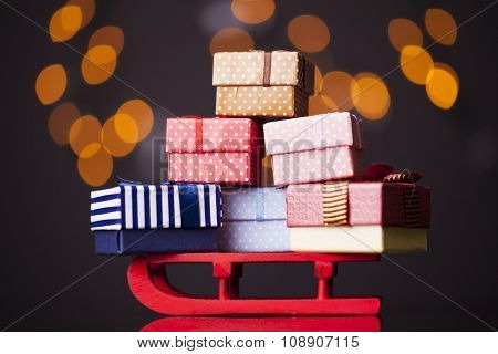 Wooden red sled full of gift boxes on dark background