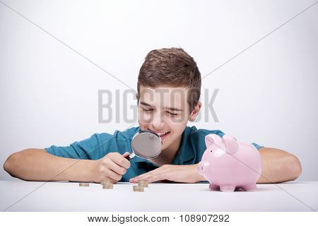 Boy with magnifying glass looking to his savings