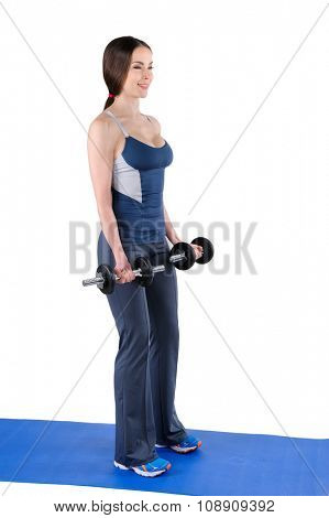Young woman fitness instructor shows starting position of standing dumbbell dumbbell biceps curl, isolated on white
