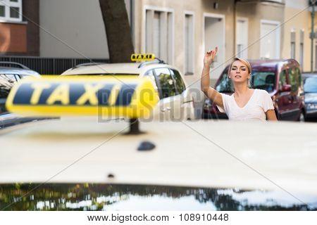 Woman Raising Arm To Hail Taxi On Street