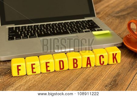 Feedback written on a wooden cube in a office desk