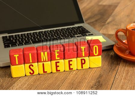 Time to Sleep written on a wooden cube in a office desk