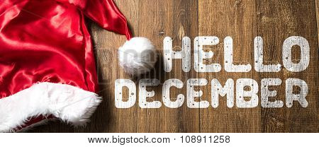 Hello December written on wooden background with Santa Hat