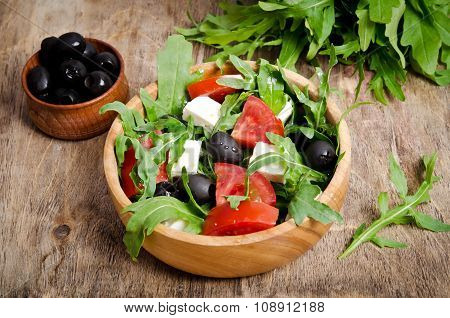 Salad With Tomatoes And Olives On Wooden Background.