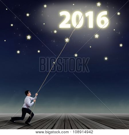 Businessman Pulling Numbers 2016 At The Sky