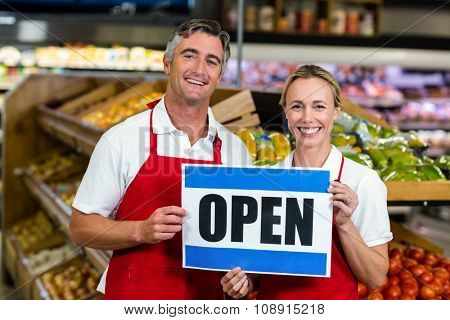 Smiling colleagues holding sign together at supermarket