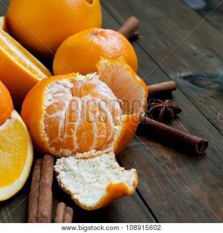 Tangerines, Oranges And Cinnamon Sticks On A Wooden Table