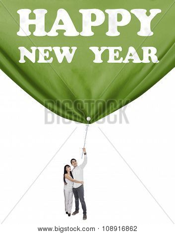 Couple Drag A Banner New Year In Studio