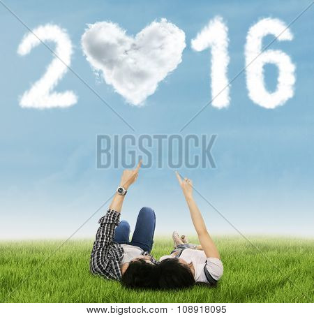 Couple Relaxing On Grass Under Numbers 2016